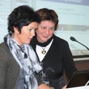 Liv Margot Sviland og Hanne Dagfinrud som leter etter noe på datamaskinen