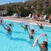 Revmatikere som trener i utebasseng med pøller over hodet på Gran Canaria