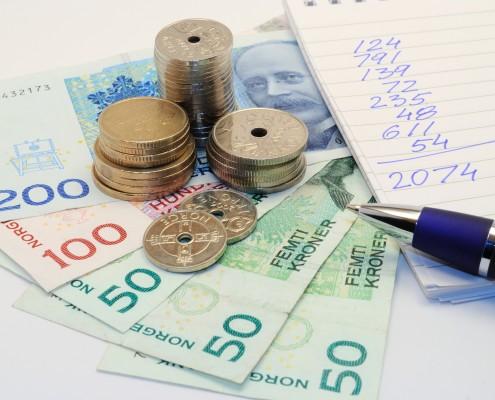 Norske penger, penn og blokk med regnestykke