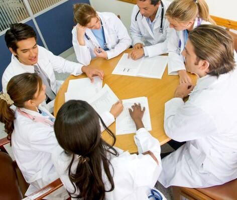 Leger diskuterer rundt et bord