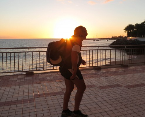 Mann med sekk på gåtur langs strandpromenaden på Gran Canaria