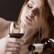 Kvinne med rødvinnsglass og lukkede øyne
