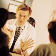 Lege snakker med to pasienter