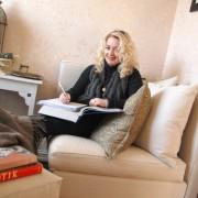 Lillann Wermskog i sofaen med bøker hun leser til studiene