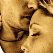 Mann som kysser pannen til en kvinne som har hodet på brystet hans