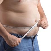 Mann med stor mage som måler med målebånd rundt livet