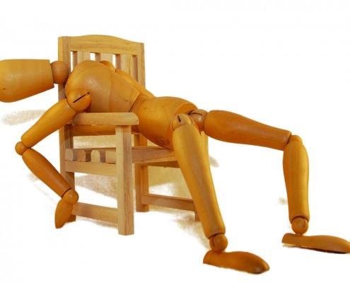 Trefigur som ligger slapt over en trestol