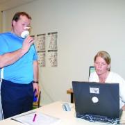Mann som tar spirometriprøve og fysioterapeut som sjekker datamaskinen