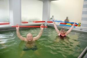 Mann og dame med stokker som trener i et basseng av stål