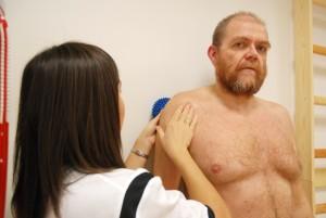 Pasienten står med ryggen mot veggen og en liten ball bak ene skulder, og osteopaten står og veileder og retter på skulder