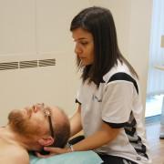 Pasienten ligger på ryggen, osteopaten jobber med fingren under hode ved nakken
