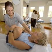 Britha på behandlingsbenk og fysioteraput som hjelper med strekking