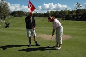 Bilde av et par på golfbane, hvor hun skal putte og han holder flagget
