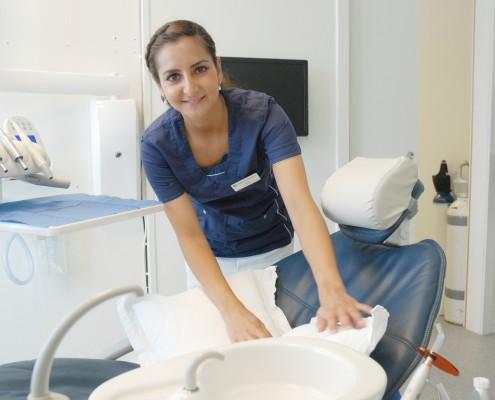 Kvinnelig tannlege legger puter i tannlegestol