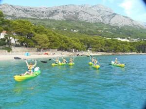 Mange mennesker i gule kajakker med padleårene i været