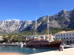 Stor trebåt til kai i Makarska med Bokovo-fjellet i bakgrunnen