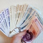 Norske sedler i vifte i en hånd