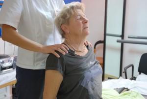Tove sitter mens hun retter ryggen og fysioterapeuten hjelper til med tøyingen