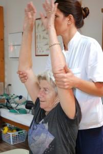 Fysioterapeuten strekker armene til en sittende Tove opp i luften