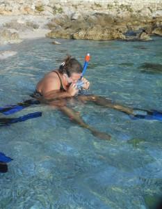 Dame sitter i vann med dykkermaske og snorkel