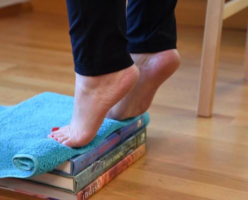 Dame hever føttene opp fra en stabel med bøker