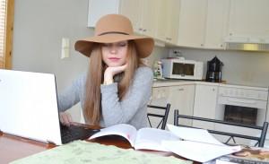 Karoline Brevik sitter ved kjøkkenbordet med bøker og PC