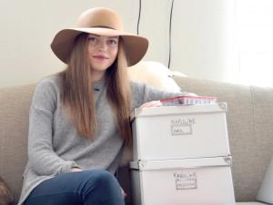 Karoline Brevik sitter i sofaen med to store esker