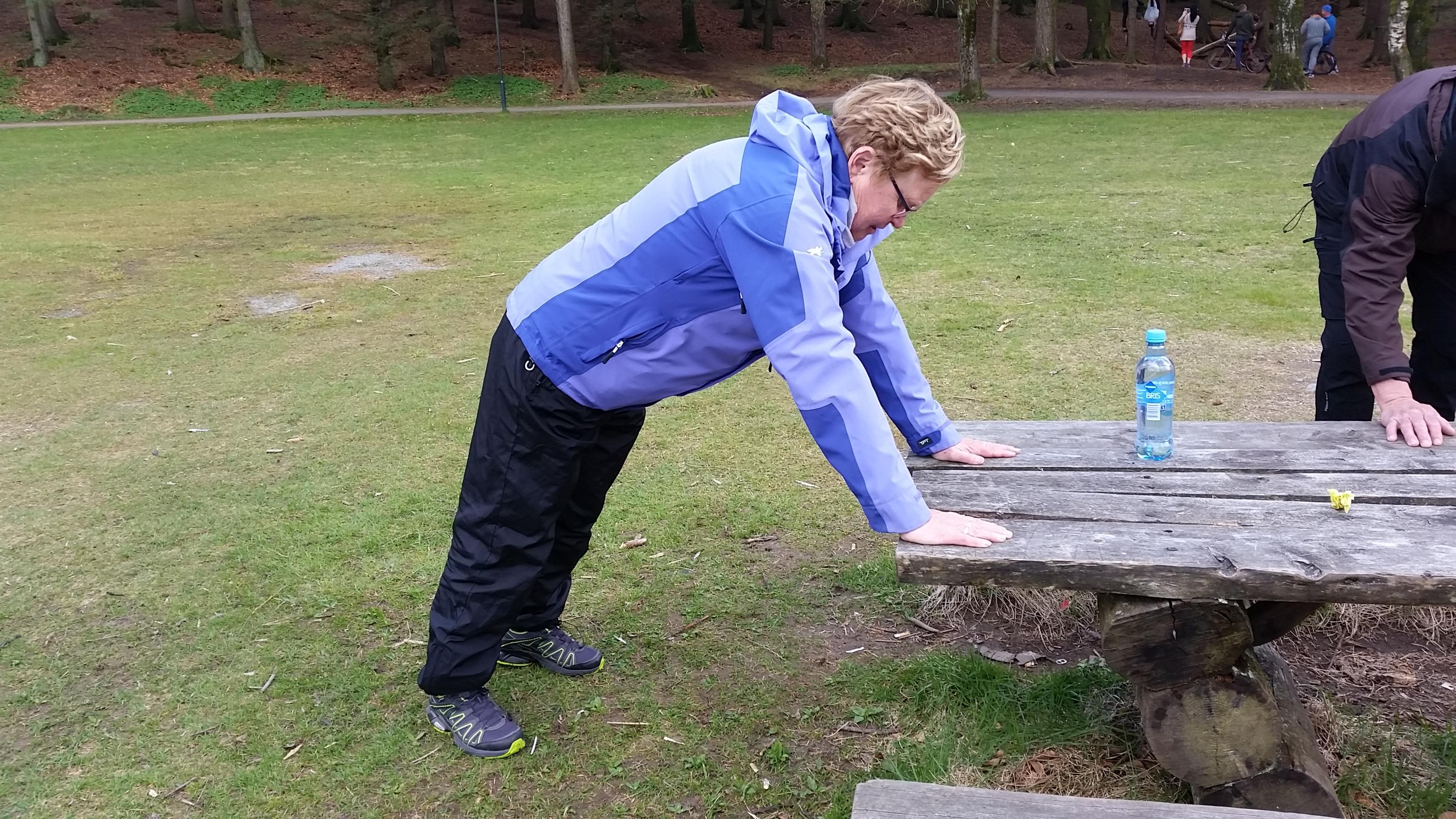 Dame som gjør pushups mot et utebord