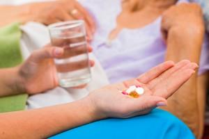 Hånd med piller og vannglass foran en sengeliggende dame i bakgrunnen