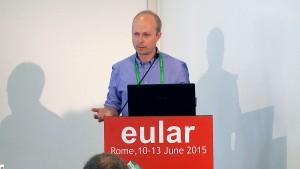 Foto av Dr. Ulf Lindstrøm på talerstol under Eular-konferanse 2015