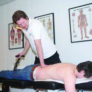 Kiropraktor som presser på ryggen til pasienten på benken