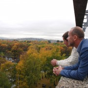 To men som står på en tak terrasse og ser utover landskapet