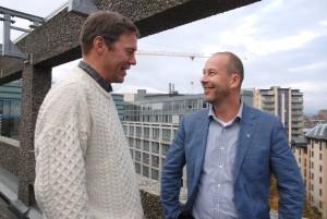 To menn i en dialog på en takterrasse, ser andre bygninger i bakgrunnen