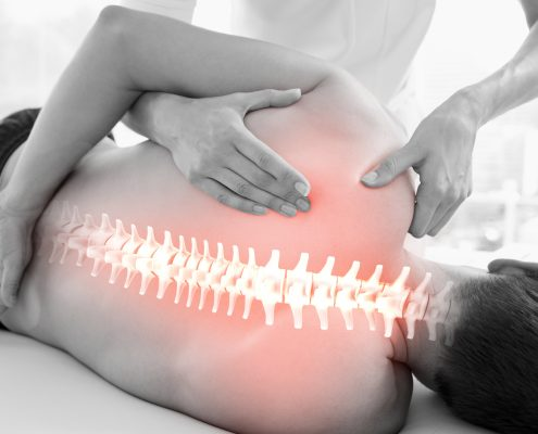 Pasient med lysende ryggrad og manuellterapeut som mobiliserer skulder.
