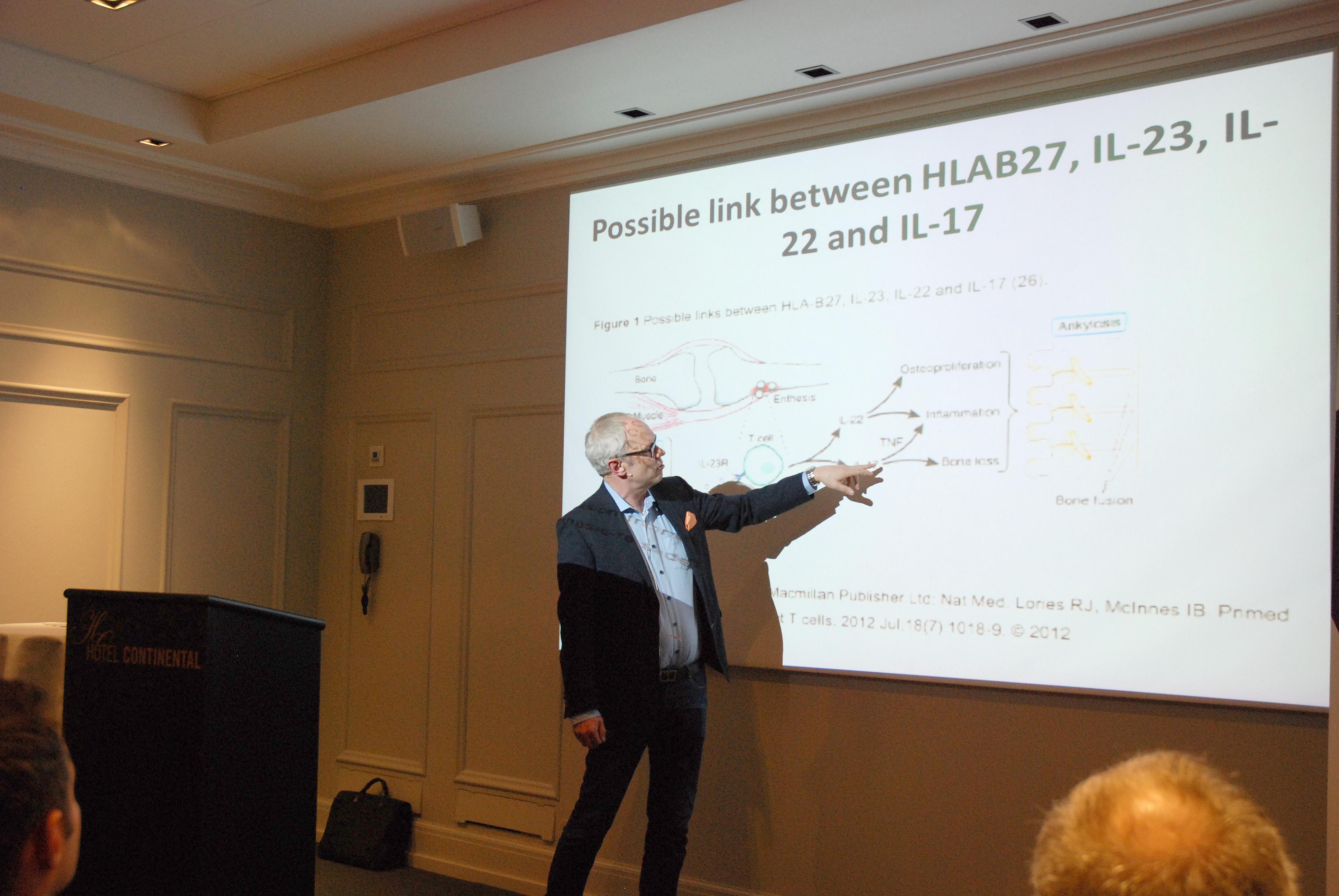 Mann peker på lysbilde under foredrag