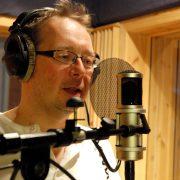 Mann i studio med mikrofon og høretelefoner