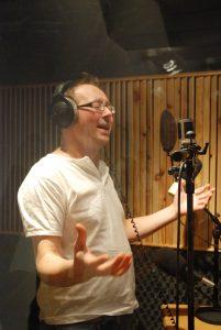 Mann med øretelefoner og mikrofon som joiker i studio