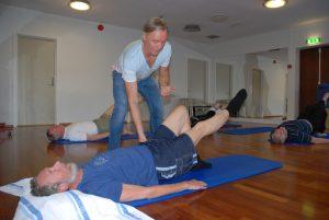 Terapeuten veileder pasienten som ligger på gulvet og gjør øvelser