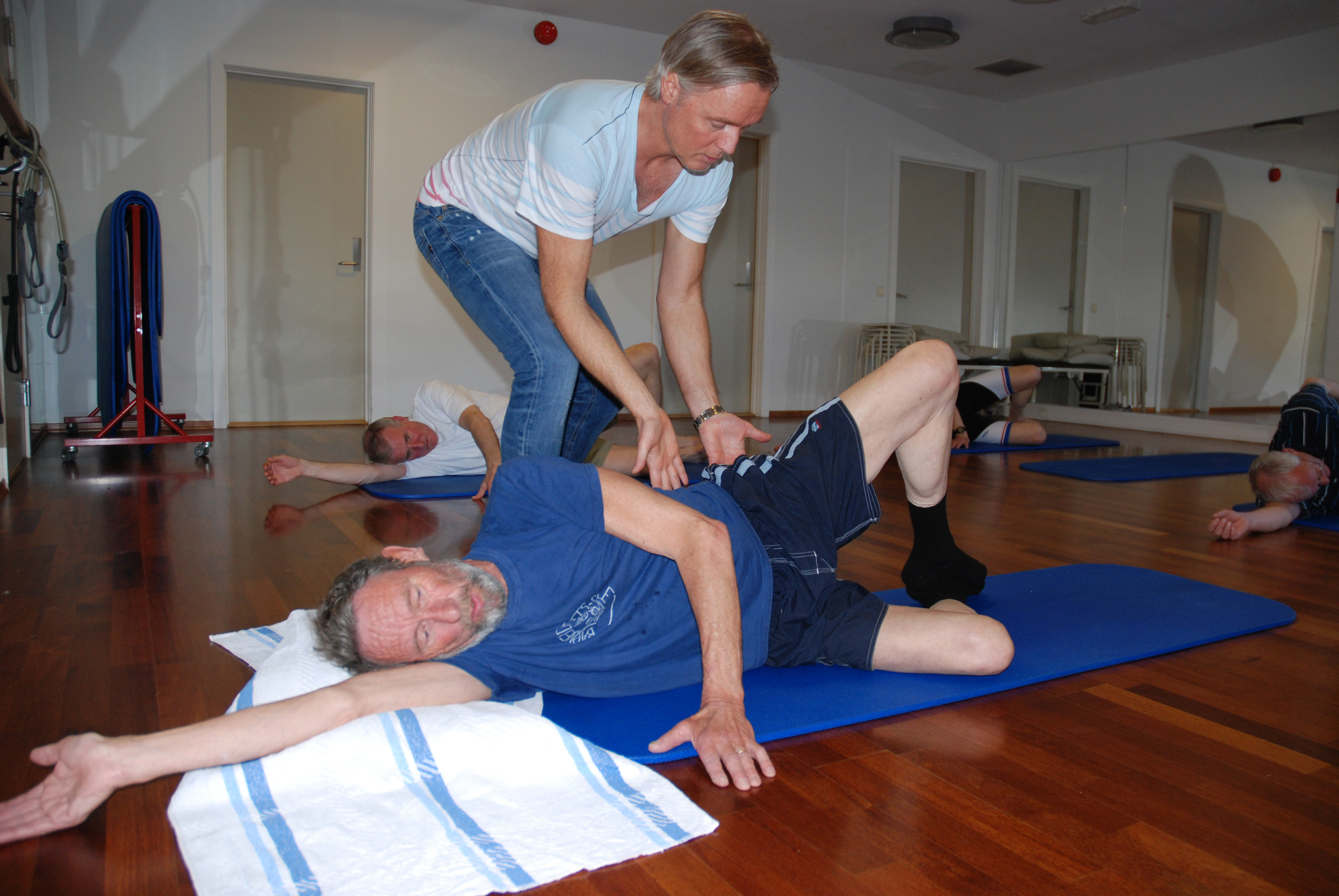 Fysioterpeuten veileder øvelsene til pasienten på gulvet