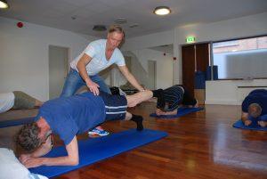 Fysioterapeuten veileder pasienten på gulvet