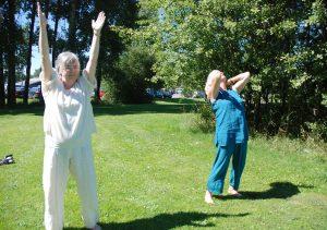 To damer står på wn grønn plen og gjør Qi Gong-øvelser
