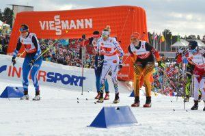 Flere kvinnelige skiløpere på stadioen under en staffet