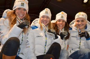 Fire kvinner sitter på huk og viser frem sølvmedaljen de har vunnet.
