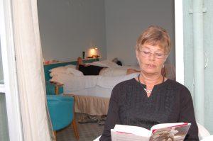 Dame leser, mens mannen ligger på sengen i bakgrunnen