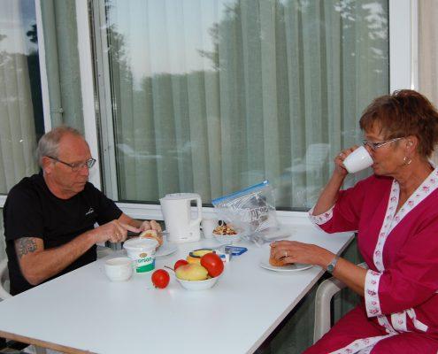 Mann og dame ved et frokostbord ute