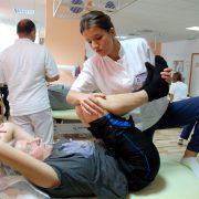 Fysioterapeut med en fot på benken og tøyer korsryggen til pasienten