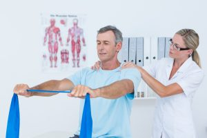 Mann trener med strikk mens fysioterapeuten veileder