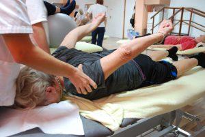 Pasient ligger på benken og løfter armene bakover mens fysioterapeut veileder