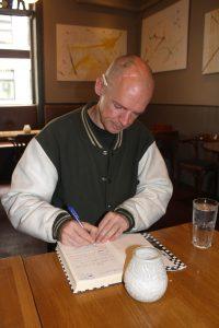 Mann som sitter på kafe og skriver i en notatbok