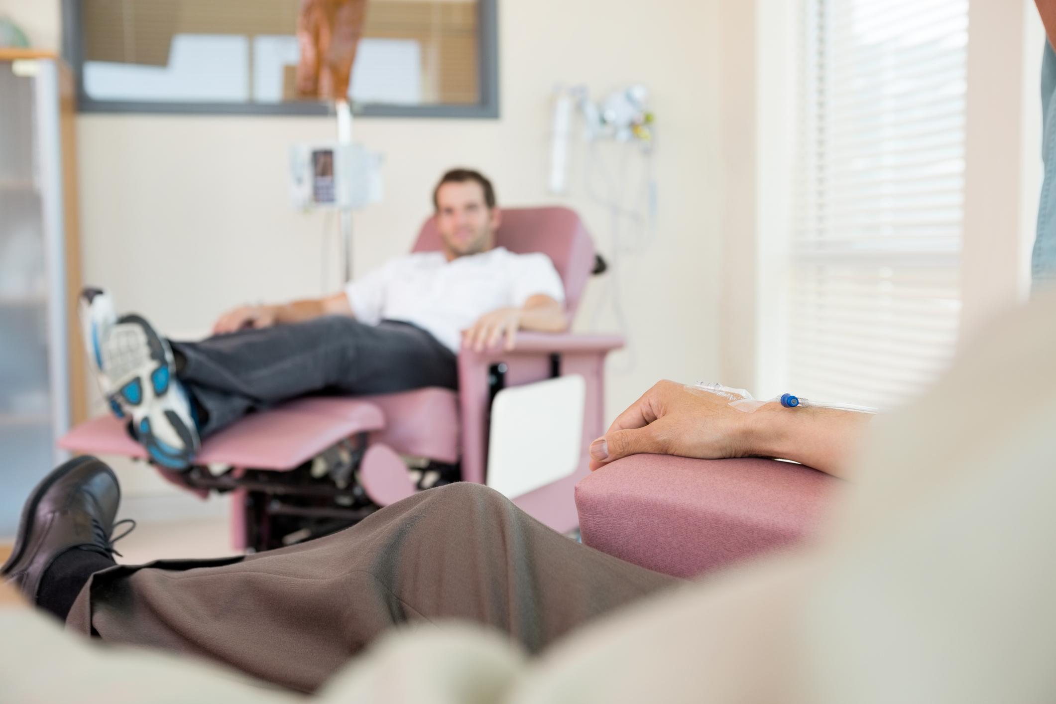 Mann sitter på sykehus og får intravenøs medisin